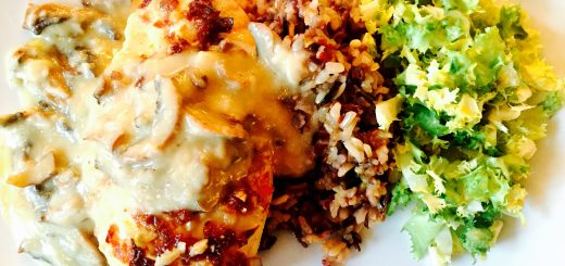 Roasted chicken breast in creamy mushroom sauce with wild rice and frisée salad