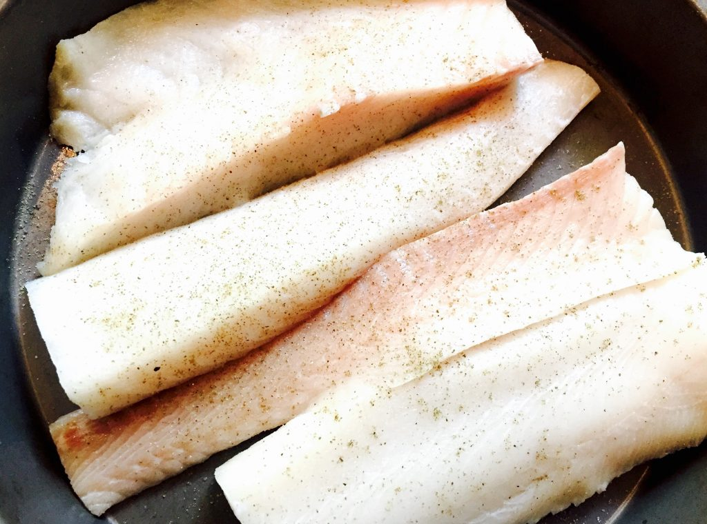 A large, fresh cod fillet cut into serving-friendly portions, then seasoned with kosher salt & freshly ground black pepper